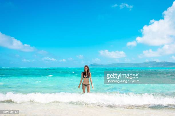 Portrait Of Woman Standing On Shore At Beach Against Sky