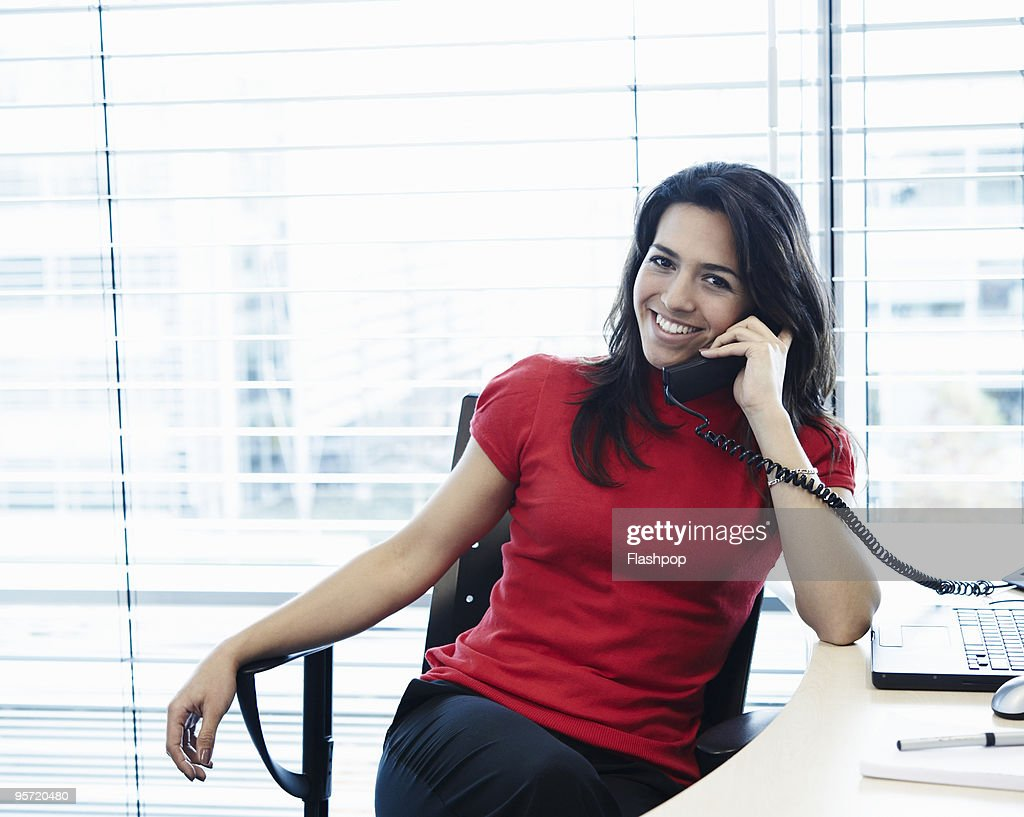 Portrait of woman talking on the telephone at work : Stock Photo