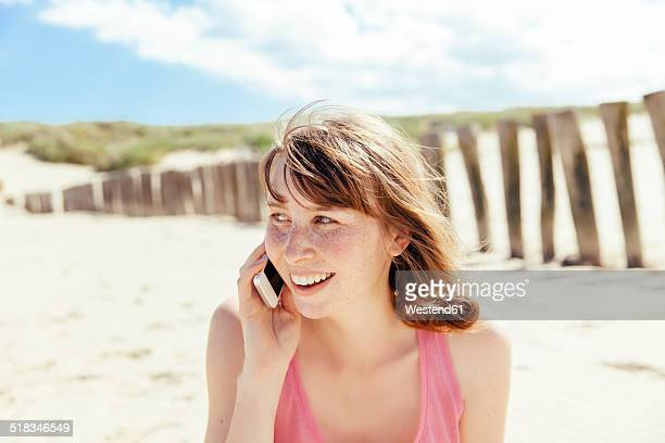 Portrait of woman telephoning with her smartphone on the beach