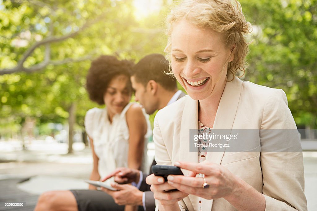 Portrait of woman text messaging with man and woman in background : Foto de stock