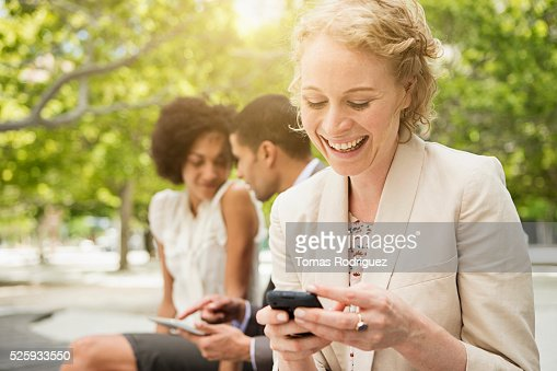 Portrait of woman text messaging with man and woman in background : Stock Photo