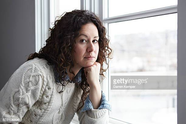 Portrait of woman thinking by window