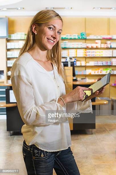 Portrait of woman using digital tablet to check medicine online in pharmacy