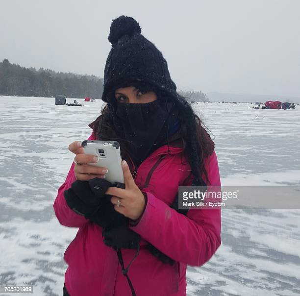Portrait Of Woman Using Phone On Frozen Lake
