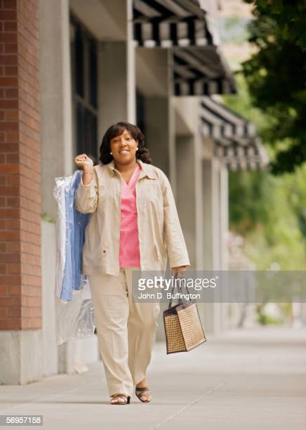Portrait of woman walking down street carrying dry cleaning