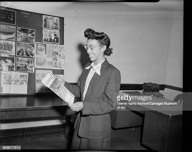Portrait of woman wearing dark pinstriped suit and eyeglasses holding US Navy brochure in interior with bulletin board with military pictures circa...