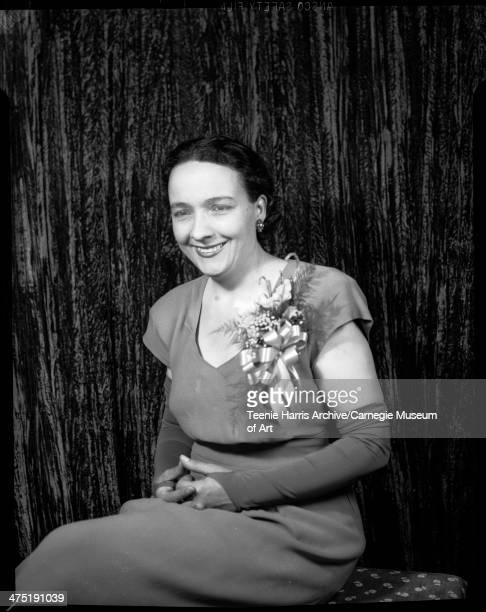 Portrait of woman wearing dark short sleeved crepe dress and fingerless gloves posed in front of dark crushed velvet curtain for Curtis Wesley...