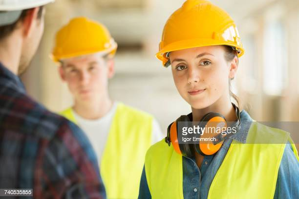 Portrait of woman wearing hard hat and hi vis vest, co-workers in background
