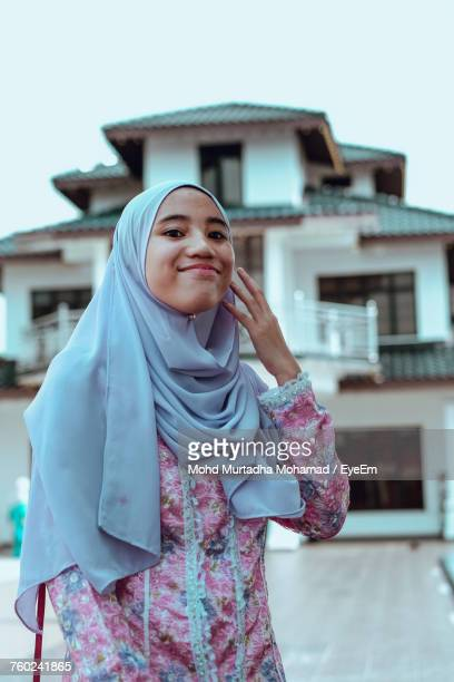 Portrait Of Woman Wearing Hijab While Standing Against House