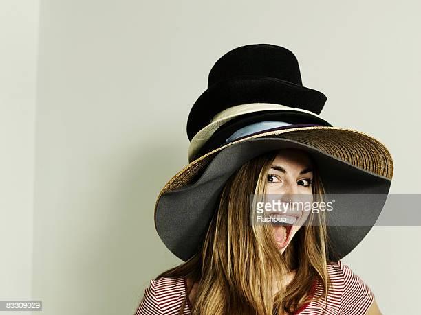 Portrait of woman wearing lots of hats