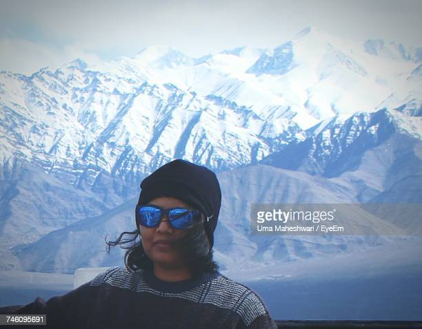 Portrait Of Woman Wearing Sunglasses During Winter Against Mountains