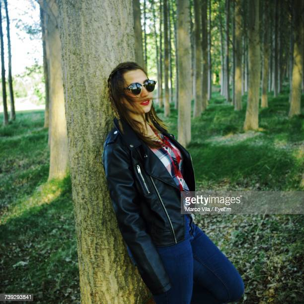 Portrait Of Woman Wearing Sunglasses While Leaning On Tree At Forest