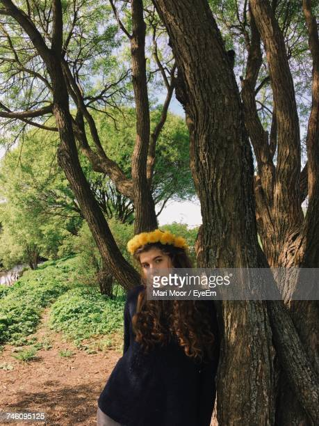 Portrait Of Woman Wearing Wreath While Leaning On Tree Outdoors