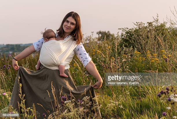 Portrait Of Woman With Baby Carrying In Fabric While Holding Skirt On Field Against Sky