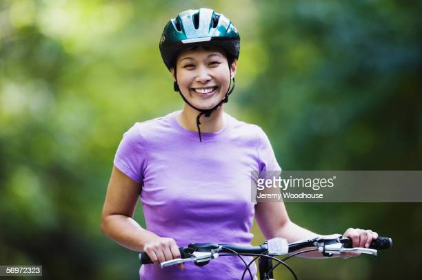 Portrait of woman with bike wearing bike helmet