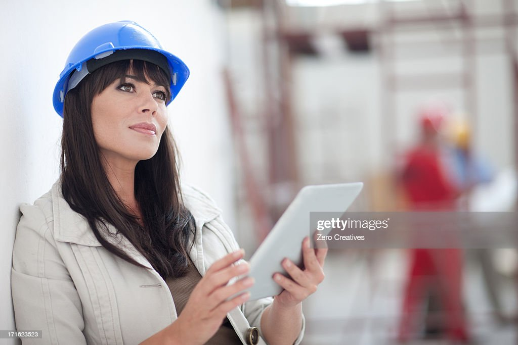 Portrait of woman with blue hard hat and digital tablet