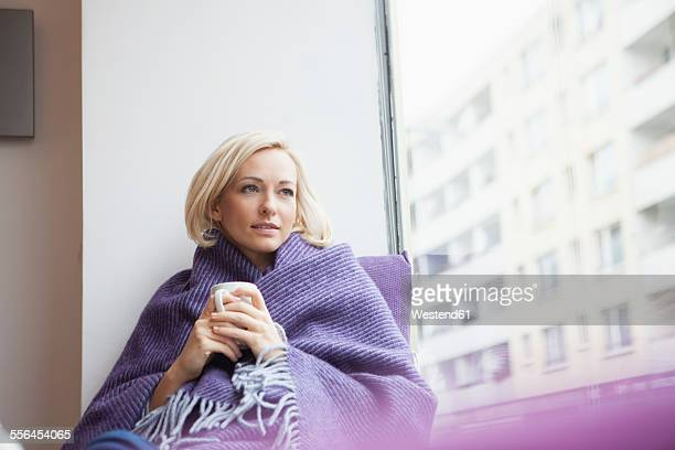 Portrait of woman with cup and woolen blanket looking through window