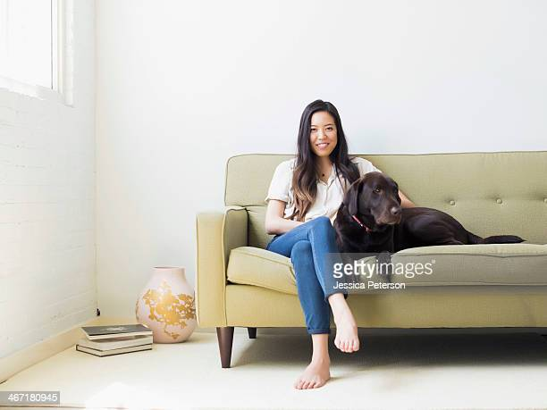 Portrait of woman with dog sitting on sofa