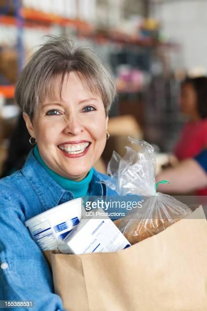 Porträt der Frau mit gespendete Lebensmittel-Tasche in Spende-Center