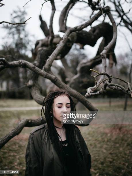 Portrait of woman with dreadlocks in forest