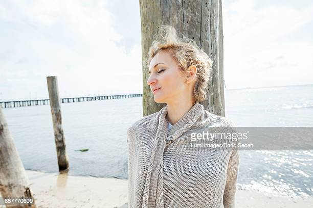 Portrait of woman with eyes closed on beach