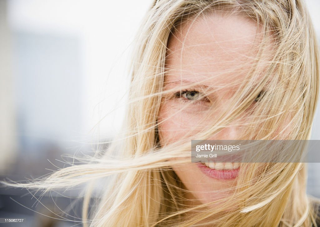 Portrait of woman with hair blowing across face : Stock Photo