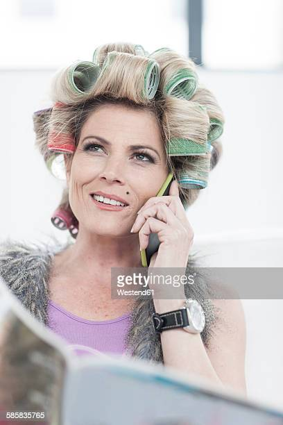 Portrait of woman with hair curlers and magazine talking on phone