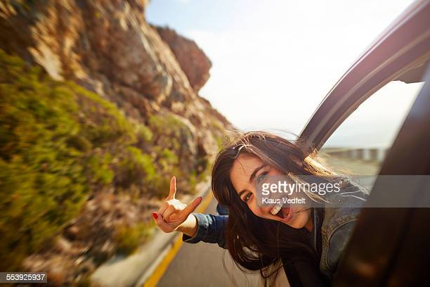 Portrait of woman with head out of car window