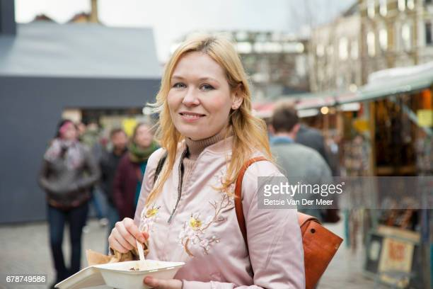 Portrait of woman with healthy take away food standing  in urban market.