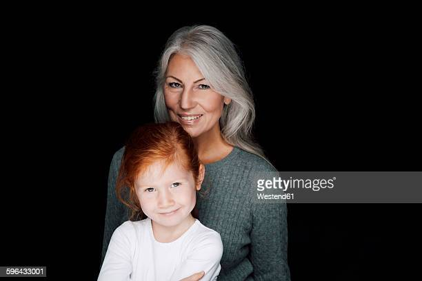 Portrait of woman with her little granddaughter in front of black background