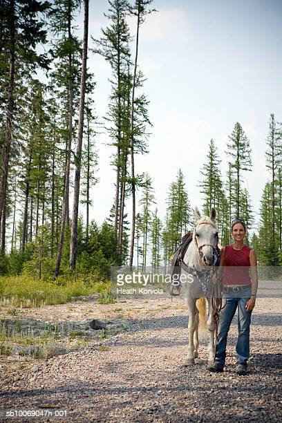 Portrait of woman with horse in forest