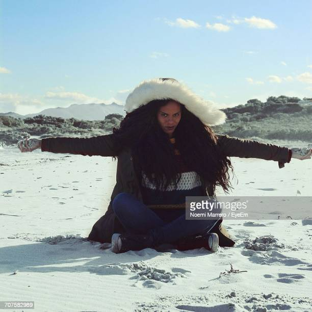 Portrait Of Woman With Long Hair Sitting On Snow Covered Field Against Sky