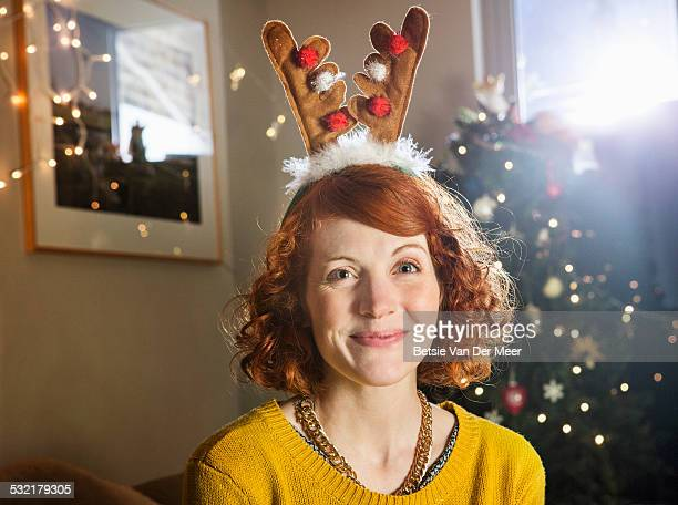 Portrait of woman with reindeer antlers.