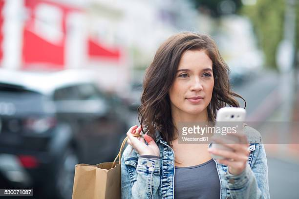 Portrait of woman with shopping bag and smartphone walking on the street