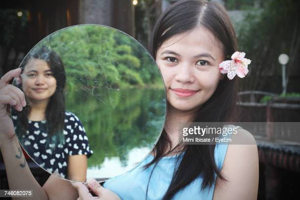 Portrait Of Woman With Sister Reflecting In Mirror