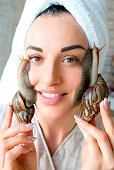 portrait of smiling young darkhaired woman with snails achatina giant on her face