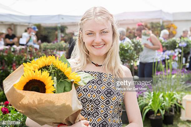 Portrait of woman with sunflowers at flower market