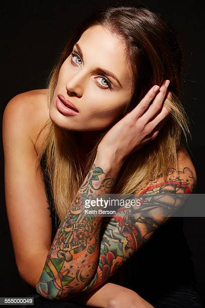 Portrait of woman with tattooed arms