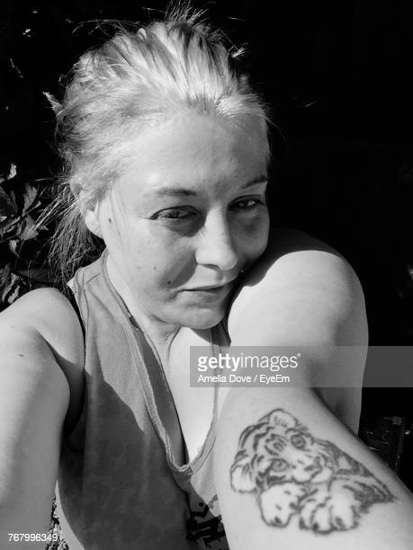 Portrait Of Woman With Tiger Tattoo On Forearm