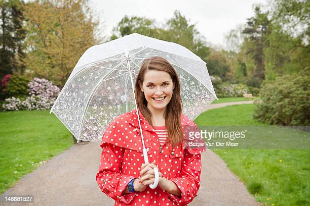 Portrait of woman with umbrella walking in park.