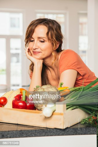 Portrait of woman with wooden box of vegetables