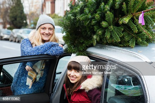 Portrait of women with their christmas tree on roof of the car.