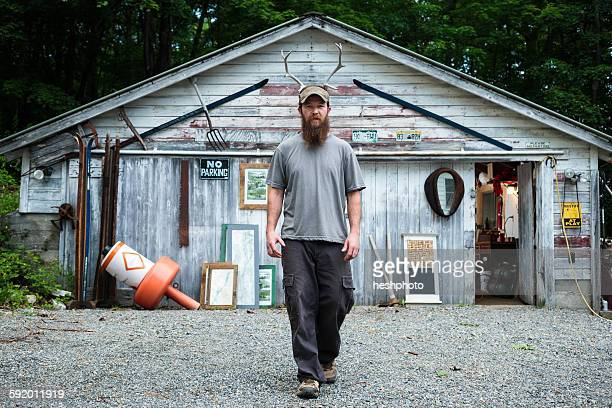Portrait of wood artist in front of workshop