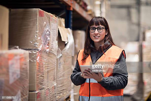 Portrait of worker checking box in warehouse