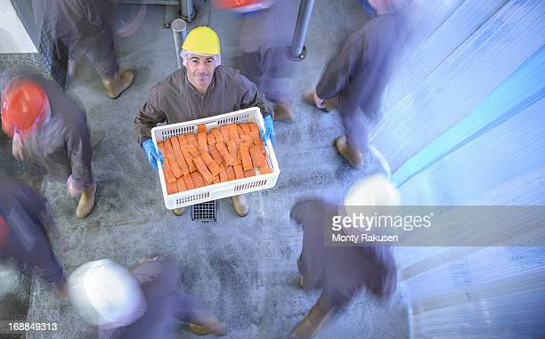 Portrait of worker holding basket of smoked salmon fillets in busy food factory