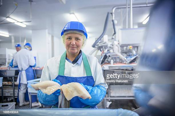 Portrait of worker holding fresh fish fillets in food factory