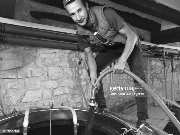 Portrait Of Worker Holding Hose While Pouring Liquid In Container At Factory