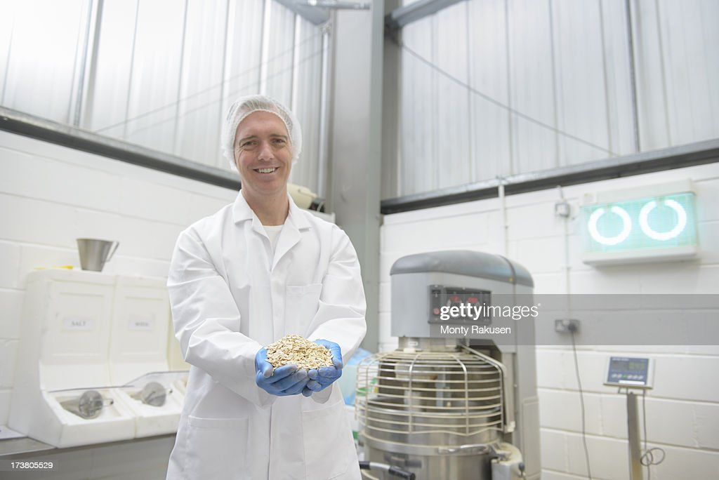 Portrait of worker holding oats in biscuit factory, smiling