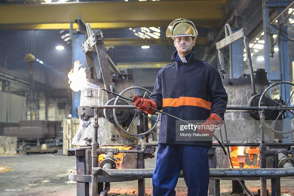 Portrait of worker in foundry wearing visor and holding flame gun