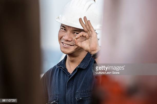 Portrait of worker on oil tanker making ok gesture